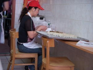 Woman hand making rows upon rows of dumplings
