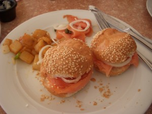 Smoked salmon, cream cheese, onion, tomato, and capers on rolls with breakfast potatoes