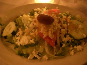 Salad topped with pieces of crumbled feta