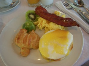 Eggs benedict, croissant, kiwi, scrambled eggs, bacon