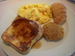 French toast, scrambled eggs, croissant, and some sort of fritter