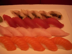 Mackerel on top, followed by tuna, yellowtail, and salmon sushi
