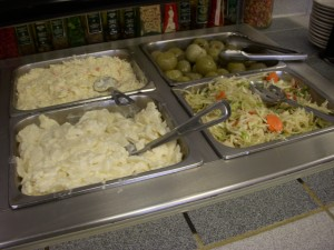 Potato salad, cole slaw, health salad, and pickled green tomatoes