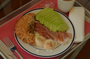 Sous vide eggs, half an everything bialy, honeydew, and prosciutto, plus coffee and a mimosa