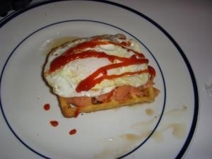 Waffle layered with maple syrup, smoked salmon, a sunnyside up egg, ketchup, and sriracha