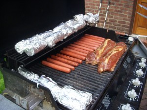 Hot dogs, ribs, and corn wrapped in foil on the grill