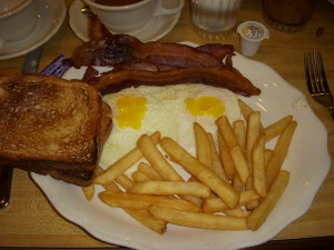 Two eggs over easy, bacon, french fries, and toast