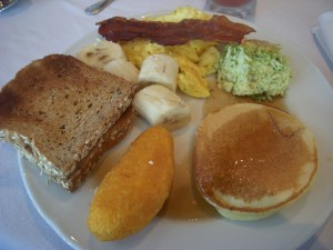 Whole wheat toast, bananas, scrambled eggs, bacon, broccoli frittata, pancake, fried yuca filled with cheese