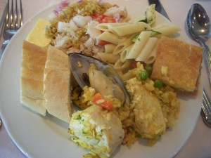 Paella with seafood and meat, french bread, crab salad with quinoa, pasta salad, ham and cheese tart
