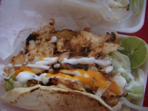 Chicken shawarma on pita topped with garlic sauce and hot sauce