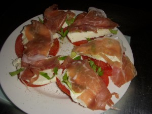 Fresh caprese salad topped with prosciutto
