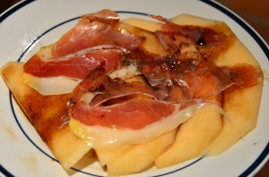 Slices of crenshaw melon with prosciutto and balsamic syrup