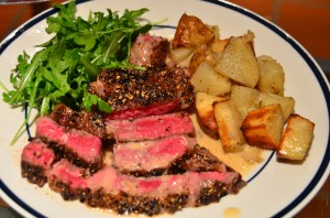 Steak au poivre with foie gras fat roasted potatoes and arugula salad